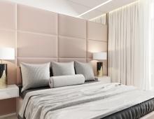 Мягкие панели изголовья, обтянутые атласной тканью цвета мокко, делают интерьер спальни элегантным